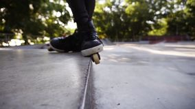 Closeup of man`s rollers on the edge of parapet. Young roller performing stunts on roller skates. Sport and leisure. Concept stock video footage