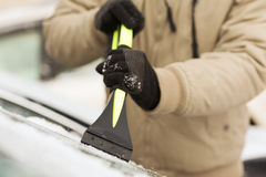 Closeup of man scraping ice from car Royalty Free Stock Photography
