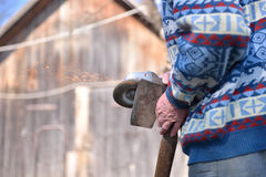 Closeup of man sharpen an ax using electric grinder. Sparks w Stock Photography