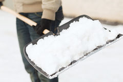 Closeup of man shoveling snow from driveway Royalty Free Stock Images