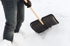 Closeup of man shoveling snow from driveway Royalty Free Stock Photography