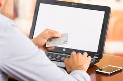 Closeup of man sitting by desk with laptop Royalty Free Stock Image