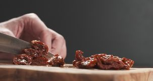 Closeup man slicing sundried tomatoes. Wide photo Stock Images