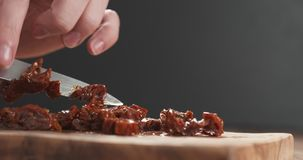 Closeup man slicing sundried tomatoes. Wide photo Royalty Free Stock Images
