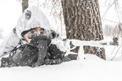 Closeup Man soldier in the winter on a hunt with a sniper rifle in white winter camouflage lies behind a tree stock images