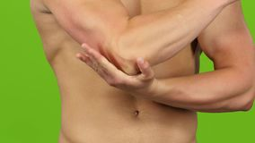 Closeup. Man suffers from pain in right elbow, green screen stock footage