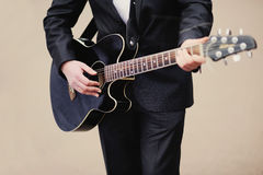 Closeup of a man in suit  playing an acoustic guitar Royalty Free Stock Photography