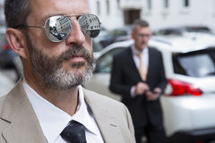 Closeup of man with sunglasses and businessman in the background Royalty Free Stock Photography