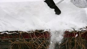 Cleaning the roof from snow. Closeup of man throw off the snowdrifts from the roof with a shovel. Consequences of heavy snowfall stock video footage