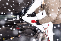 Closeup of man under bonnet with starter cables Royalty Free Stock Photos