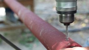 Closeup of a man using a power drill. Blacksmithing works, drilling iron tube with drill stock video