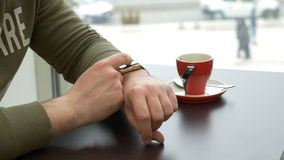 Closeup of man using smartwatch app while sitting at a table in a cafe in the city. Closeup of man using smartwatch app while sitting at table in a cafe in the stock footage