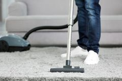 Closeup of man with vacuum cleaner cleaning carpet. At home Stock Image