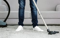 Closeup of man with vacuum cleaner cleaning carpet. At home Royalty Free Stock Photo