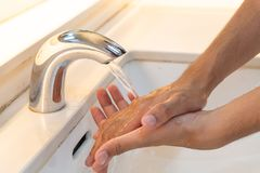 Closeup man washing hands with soap under the faucet with water. In the bathroom stock photography
