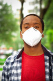 Closeup man wearing blue white square pattern shirt, covering nose and mouth with protection filter mask walking outside Royalty Free Stock Image