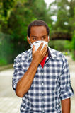 Closeup man wearing blue white square pattern shirt, covering nose and mouth with protection filter mask walking outside Royalty Free Stock Images