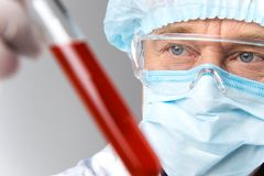 Closeup of man wearing mask looks at test tubes. Royalty Free Stock Photos
