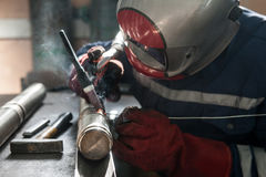 Closeup of man wearing mask welding in a workshop. Closeup of man wearing helmet welding in a workshop Stock Photos