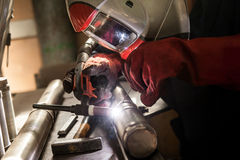 Closeup of man wearing mask welding in a workshop. Closeup of man wearing helmet welding in a workshop Royalty Free Stock Images
