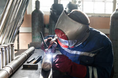 Closeup of man wearing mask welding in a workshop. Closeup of man wearing helmet welding in a workshop Royalty Free Stock Image