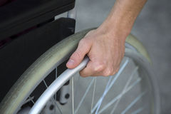 Closeup of man in wheelchair holding wheel Stock Images