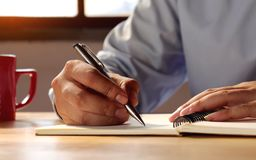 Closeup of the man who wrote the spiral notebook on the table stock photo