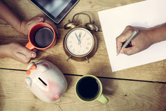 Closeup of man and woman's hands planning bargains. Picture of man's hand writing and woman's hands holding cup of coffee beside piggy-bank and alarm-clock. Top Royalty Free Stock Photography