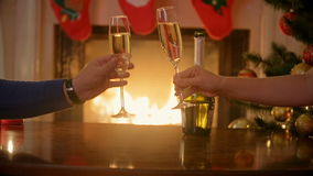 Closeup of man and woman sitting at fireplace and drinking champagne at Christmas eve stock video
