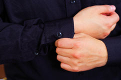 Closeup man's arm wearing suit, adjusting cufflinks using hands, men getting dressed concept Stock Image
