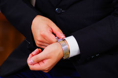 Closeup man's arm wearing suit, adjusting silver wrist watch using hands, men getting dressed concept Royalty Free Stock Image