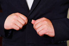 Closeup man's chest area wearing formal suit and tie, adjusting jacket buttons using hands, men getting dressed concept Royalty Free Stock Images