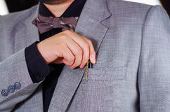Closeup man's chest area wearing formal suit and tie, placing pen in jacket pocket, men getting dressed concept Stock Photo
