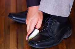 Closeup man's formal black shoes, using sponge to polish leather, men getting dressed concept Stock Photo