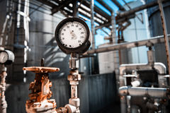 Closeup of manometer, measuring gas pressure. Pipes and valves at industrial plant Royalty Free Stock Image