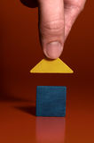 Closeup of a mans hand building a house. Closeup of a mans hand building a blue house with yellow roof Royalty Free Stock Image