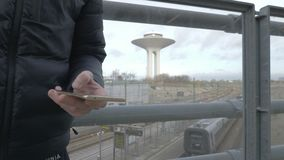 Hand typing sms mms on a smartphone. Closeup of mans hand typing sms mms on a smartphone at a train station where a train departs stock video footage