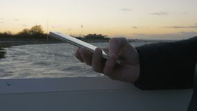 Hand typing sms mms on a smartphone. Closeup of mans hand typing sms mms on a smartphone a windy sunset night at the sea stock footage