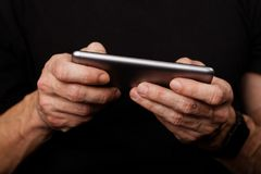 Closeup mans hand using smartphone on black background Royalty Free Stock Photo