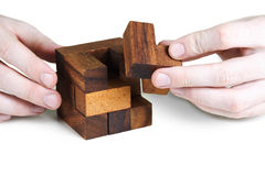 Closeup of mans hands assembling wooden cube Stock Images