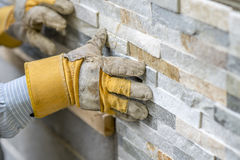 Closeup of manual worker in protection gloves pushing the tile i. Nto the cement on the wall while tiling a wall with ornamental tiles l in a DIY, renovation or Royalty Free Stock Photo