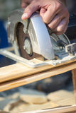 Closeup of manual worker using circular saw. To cut a wooden plank in a construction, renovation or DIY concept stock photos
