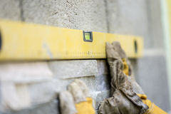 Closeup of manual worker wearing protective gloves holding a yel. Low label against a wall while placing and ornamental tile. Conceptual of construction and stock image