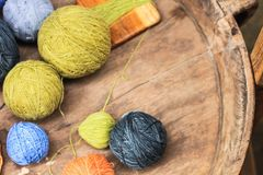 Many colored yarns roll into spheres. Placed on a wooden table stock illustration