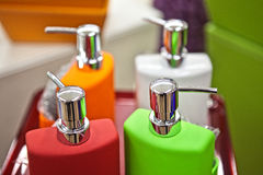 Closeup of many colorful plastic bottled flasks. Orange pink and green colors standing in raw close to each other with spray top, horizontal picture royalty free stock photo