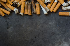 Closeup of many dirty cigarettes stock images