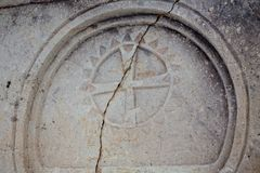 Closeup of a marble relief Maltese cross on a stone wall of an ancient Sicilian church. Closeup of a marble relief Maltese cross on a stone wall of an ancient Royalty Free Stock Image