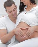 closeup marito e moglie incinta che mettono le loro mani sulla sua pancia immagine stock