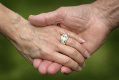 Closeup of a Married Senior Citizens Holding Hands. A loving closeup scene of a senior married couple holding hands with wedding rings Stock Images