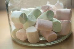 Marshmallows in glass container on wooden table backg. Closeup of marshmallows in glass container on wooden table background stock photography